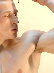 Oiled boy pumps up his biceps
