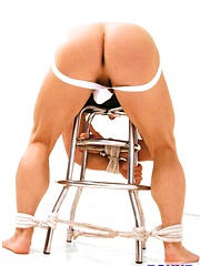 Bound jock John Magnum is tied over a stool in the middle of the locker room with his ass in the air